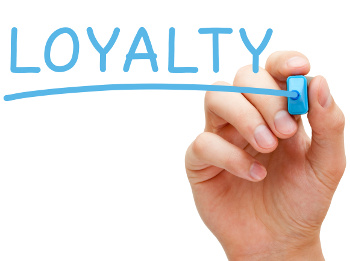 Hand writing Loyalty with blue marker on transparent wipe board.